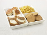"""Close up of sectioned plate with pasta, cookies, bread and biscuits"""