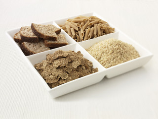 """Close up of sectioned plate with bread, pasta, rice and cereal"""