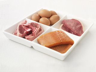 """Close up of sectioned plate with eggs, pork, salmon and steak"""