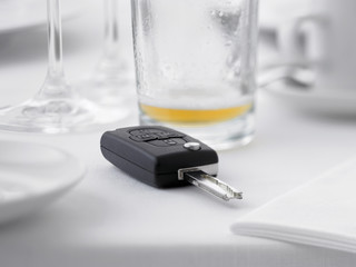 Close up of remote entry car key on restaurant table next to empty beer glass