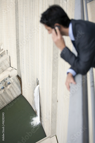 Businessman looking at water spilling from dam