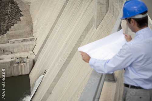 Businessman with blueprints looking at dam