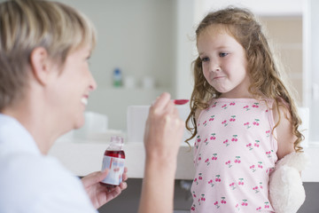 Mother giving medicine to stubborn doctor