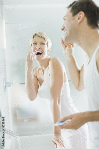 Couple brushing teeth in bathroom