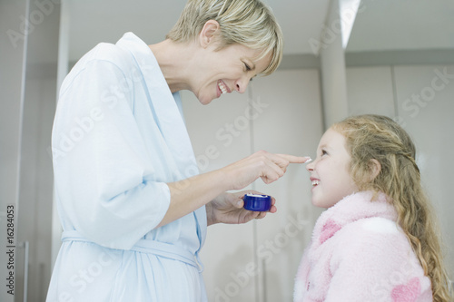 Woman applying face cream to daughter?s nose