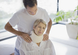 Husband helping wife in neck brace