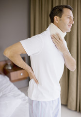 Man with neck brace and aching back