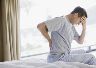 Man sitting on bed with backache and headache