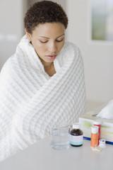Sick woman looking at medication