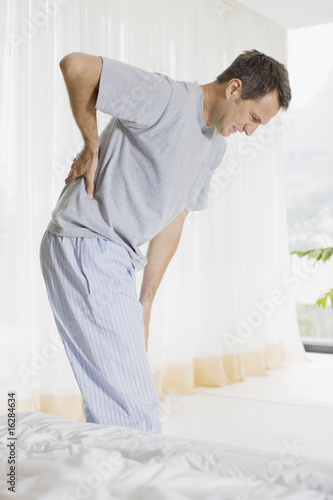 Man in bedroom with backache