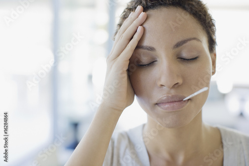 Sick woman taking her temperature