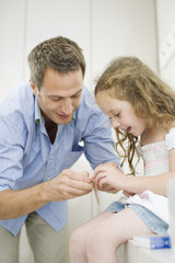 Father helping daughter with bandage