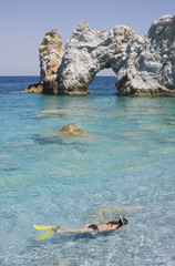 """Girl snorkeling near rock formation, Lalaria Beach, Skiathos, Greece"""