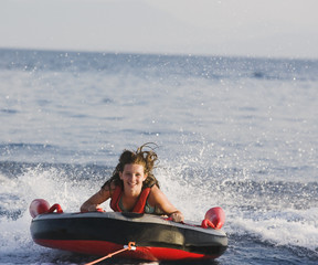 Girl riding raft in ocean
