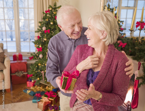 Man surprising woman with Christmas gift