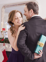 Woman peeking at Christmas gift behind man?s back