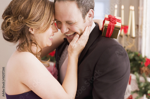 Woman holding Christmas gift and hugging man