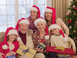 Multi-generation family wearing santa hats and holding Christmas gifts