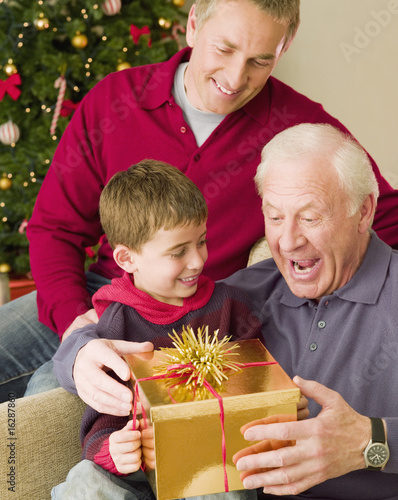 Boy giving grandfather Christmas gift