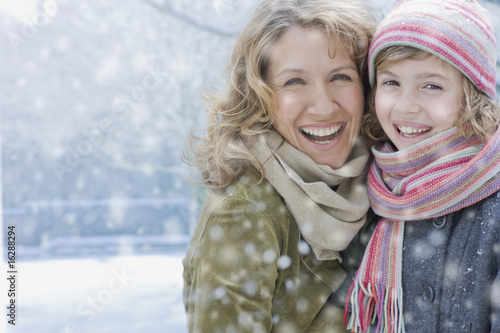 Snow falling on smiling mother and daughter