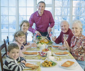 Man carving turkey for multi-generation family at table