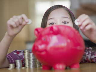 Girl putting coins in piggy bank