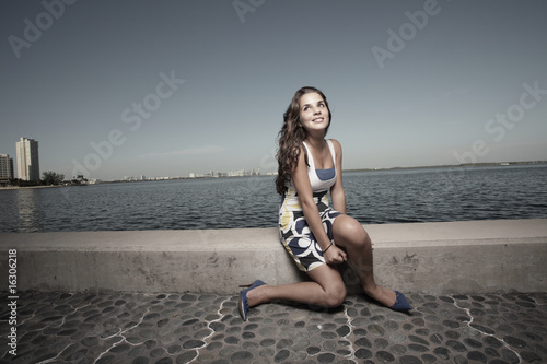 Woman sitting on a ledge by the bay