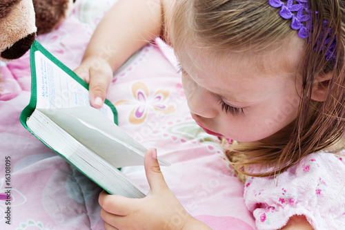 Child with damp hair is looking at her Bible before bedtime.