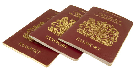 three british passports isolated on white background