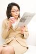 コーヒーを持ち新聞を読む女性
