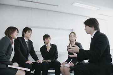 会議室でミーティングをする若い男女5人