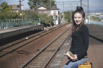 駅のホームでトランクに腰掛ける女性