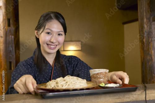 蕎麦のトレーを受け取る女性店員