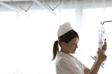 点滴の準備をする女性看護師