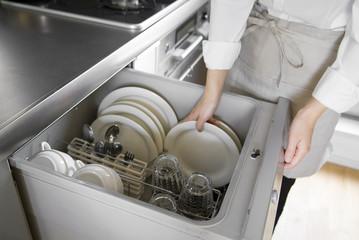 食器洗乾燥機に食器を入れる女性