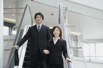 エスカレーターに乗っている男性と女性