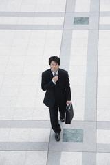 オフィスビルのロビーでネクタイを整える男性