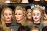 Mannequin heads with wigs in a hairdressing salon poster