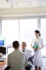 患者に問診を行う男性医師と女性看護師