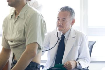 聴診器を患者の身体に当てる男性医師