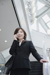 エスカレーターに乗り携帯電話で話をする女性