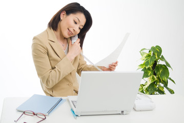 書類を確認しながら電話をする女性