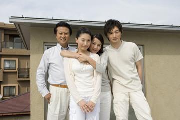 家の屋上に立つ中年夫婦と息子と娘