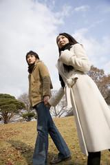 手をつないで公園を歩くカップル