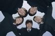 円陣を組むスーツ姿の若い男女5人