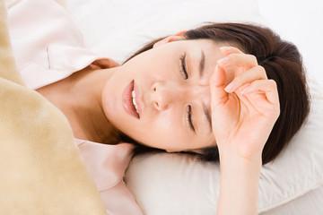 風邪をひいて寝込む女性