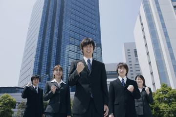 ガッツポーズをするスーツ姿の若い男女5人
