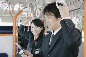バスの中で携帯電話を眺める男性と女性