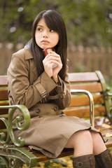 ベンチに座り缶コーヒーを持つ若い女性