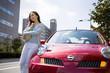 車の前に立つ若い女性